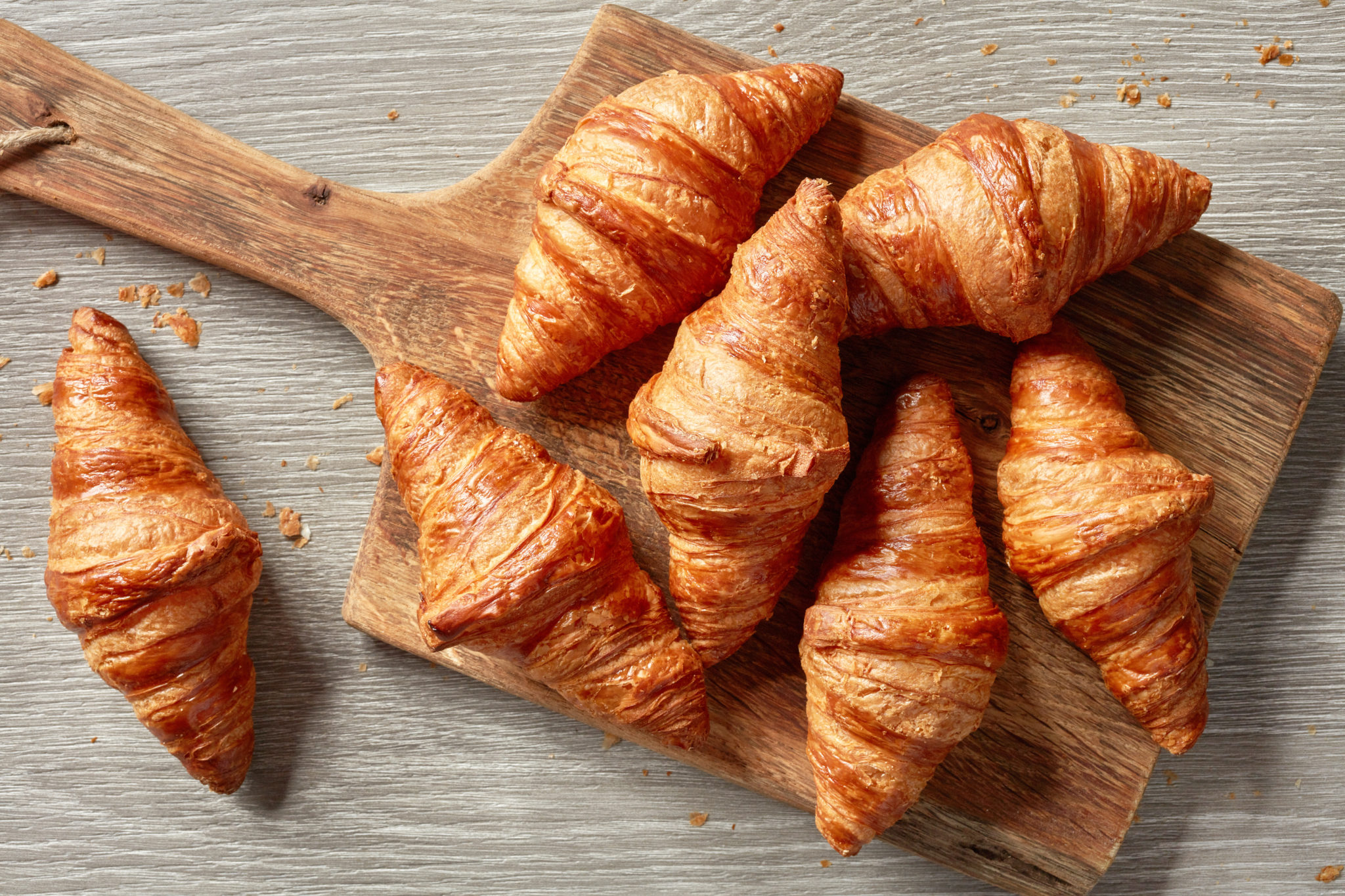 A few croissants on a wood spatula.